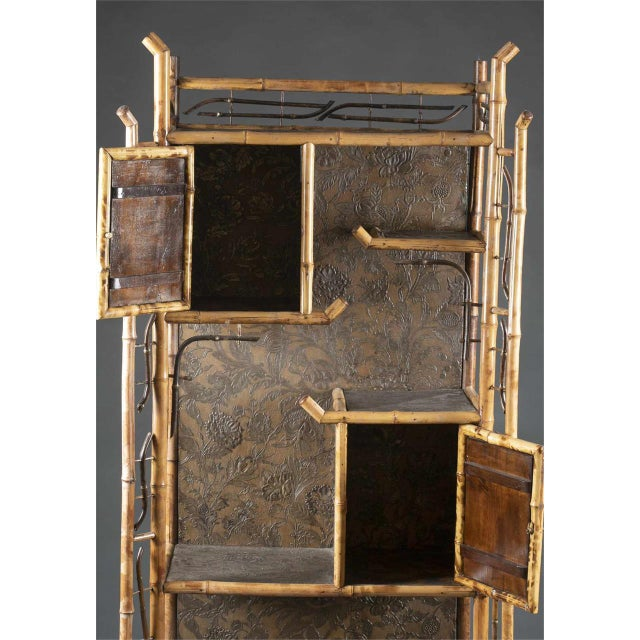 An antique Chinoiserie style bamboo open display cabinet. 19th century. It has Four display shelves, two cabinet doors...