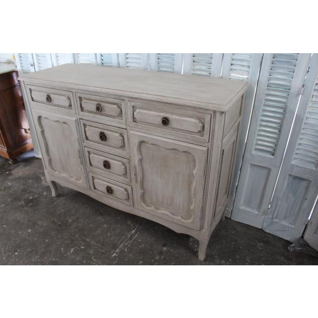 Vintage French sideboard made of solid oak with dual cabinets and spacious drawers. Beautiful carvings throughout that add...
