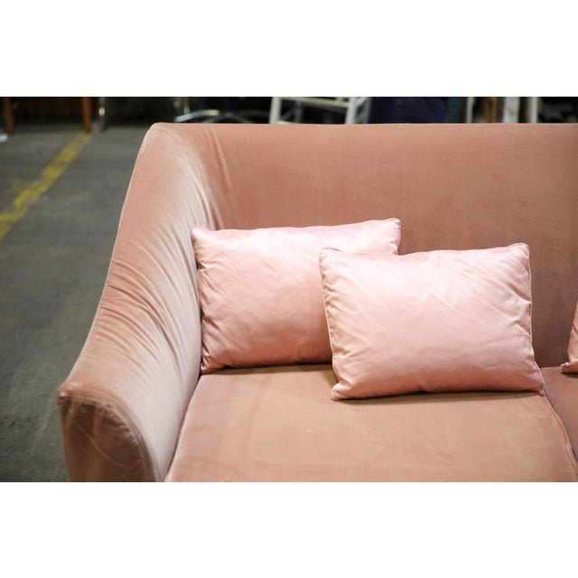 Modern sofa upholstered in pink velvet, designed by Christian Liaigre. The piece has an all-over velvet covering and comes...