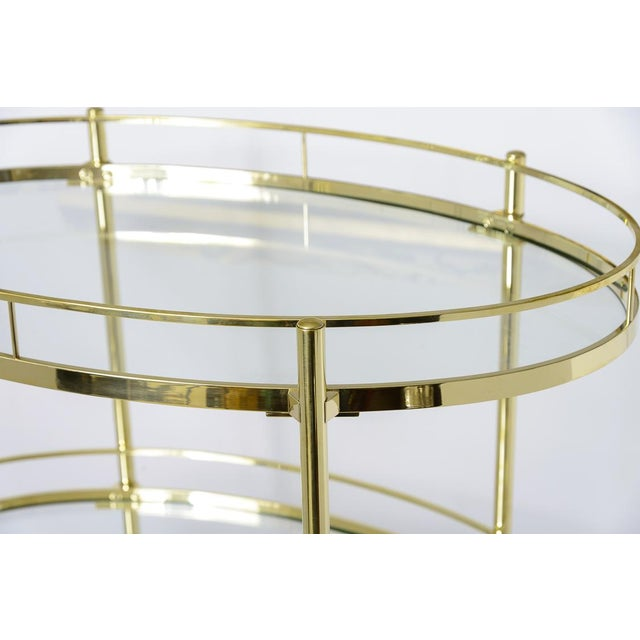 This Mid-century oval three-tiered bar/etagere signed Maxwell-Phillips, NY has been recently polished to it's original...