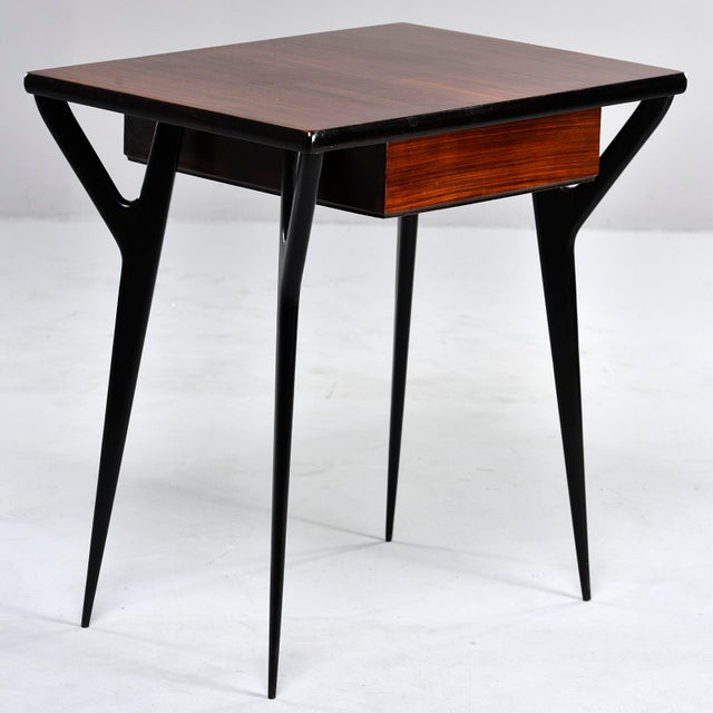 Circa early 1960s Italian desk or writing table has wishbone style tapered ebonised legs and side supports and contrasting...