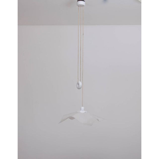 Rare early area pendant lamp by Mario Bellini in very good original condition. The donut-style counterweight is a...