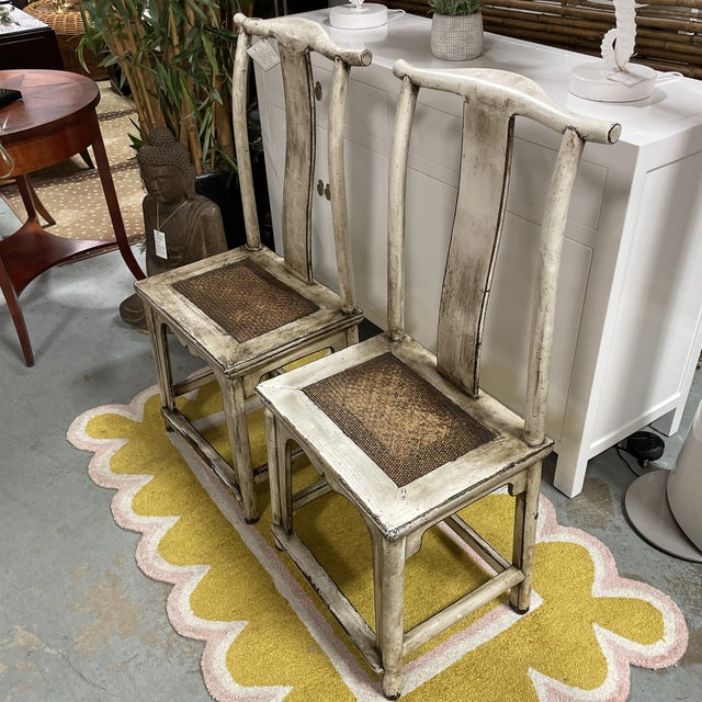Pair of vintage Asian emperor's style chairs with a cane seat. These chairs have an attractive distressed white finish....