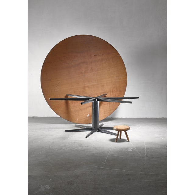 A very large (225 cm diameter) Dutch, industrial style dining table. The table has a metal six feet star base and a...