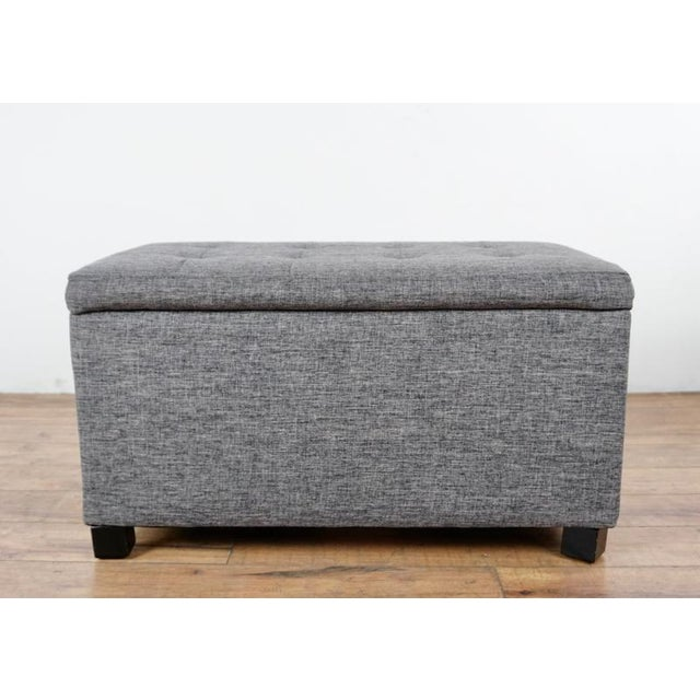 Bearing interior storage, with a lift top. Raised on wood legs. Could function as a bench or table as well. Brand is...