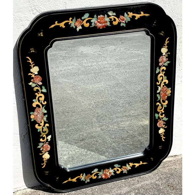 Chinese export lacquer and hardstone mirror, with various hardstone floral inlays in a gilt lacquer cartouche frame. The...