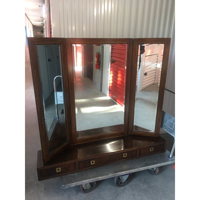 Lovely vintage piece. Trifold beveled Mirror attached to Campaign base. Great brass pulls. Incredible piece from Drexel...