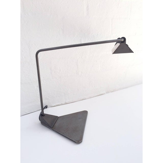 Desk lamp designed by Ron Rezek. This lamp has a raw steel finish, an adjustable arm and shade, circa 1980s.