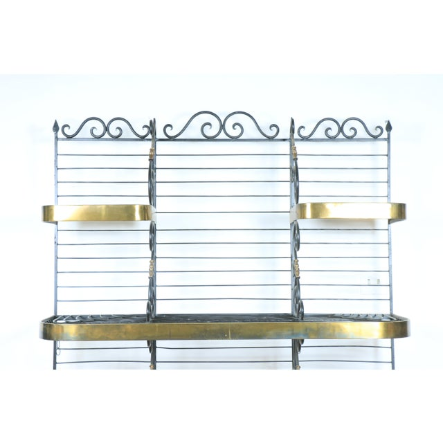 Vintage wrought iron and brass bakers rack.. Has minor scratches with no broken parts.. Base is strong and sturdy with no...