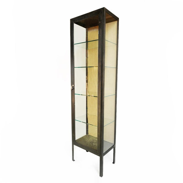 Tall industrial style sturdy iron display cabinet with four adjustable glass shelves. Backing is covered in a burlap panel.