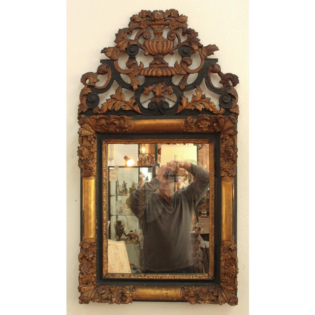 An elaborately carved giltwood frame with frame corners, an urn with flowers is surrounded by scrolls in black and gilt