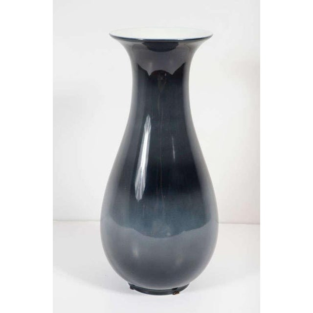 An elegant porcelain vase with a flared lip, a slender neck, a sensuously bulbous body, and a small foot; with a natural...