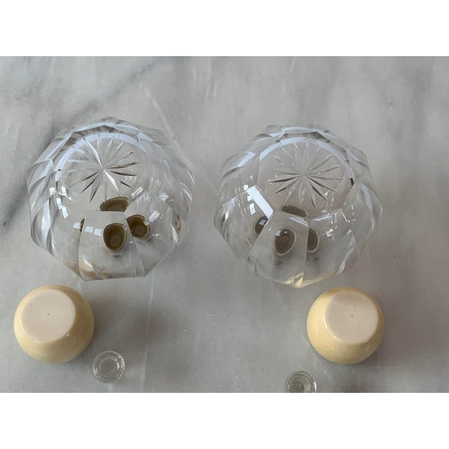 For sale is a pair of art deco style cut glass vanity cologne bottles with celluloid tops. Under the decorative tops are...