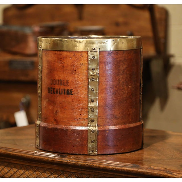 This antique grain measuring recipient was crafted in France, circa 1870. The bucket features brass strapping motifs,...