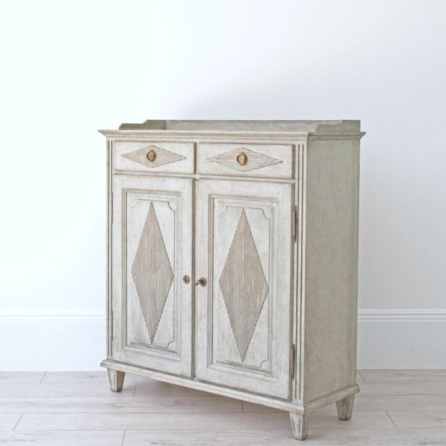 A richly carved Gustavian style buffet sideboard featuring a balcony top, fluted corners, two diamond reeded drawers over...
