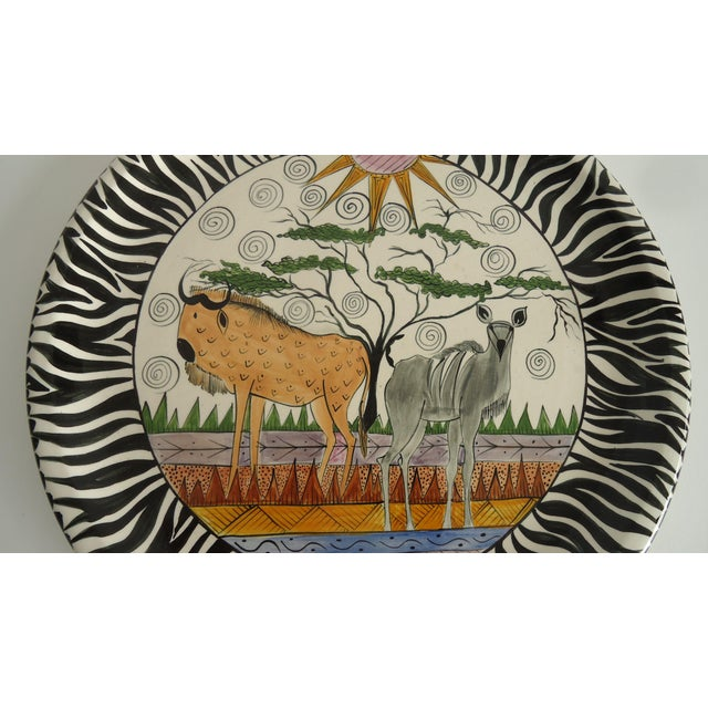 A vintage pottery platter featuring African animals & landscape by Penzo of Zimbabwe, hand painted by L Phiri. Made in 1997.