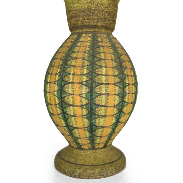 A sweet lidded ceramic vase in a classic urn form decorated with a geometric pattern in green, orange and black on yellow...