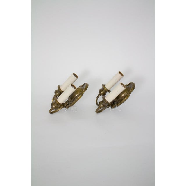 traditional pair of double arm sconces. Stamped brass, classic look. 1920's. beautifully restored finish with antique...