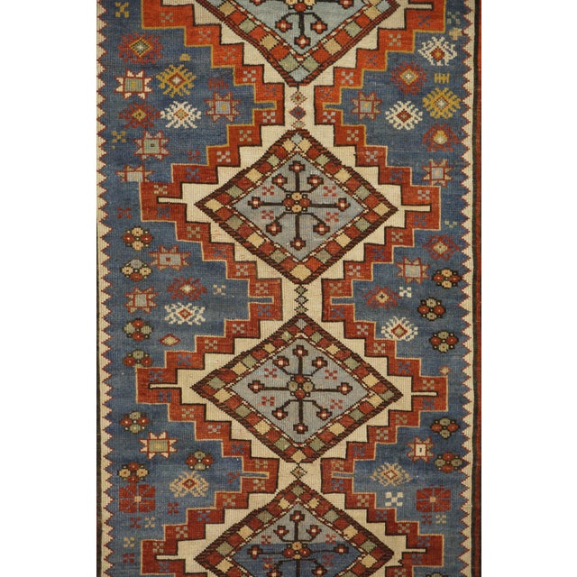 This beautiful rug is hand made. It features a geometric pattern in a vibrant combination of red and blue and ivory. With...