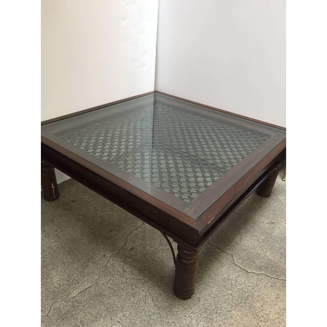 Anglo Indian style wooden coffee table with iron inset work and glass. Large coffee table in solid teak wood with...