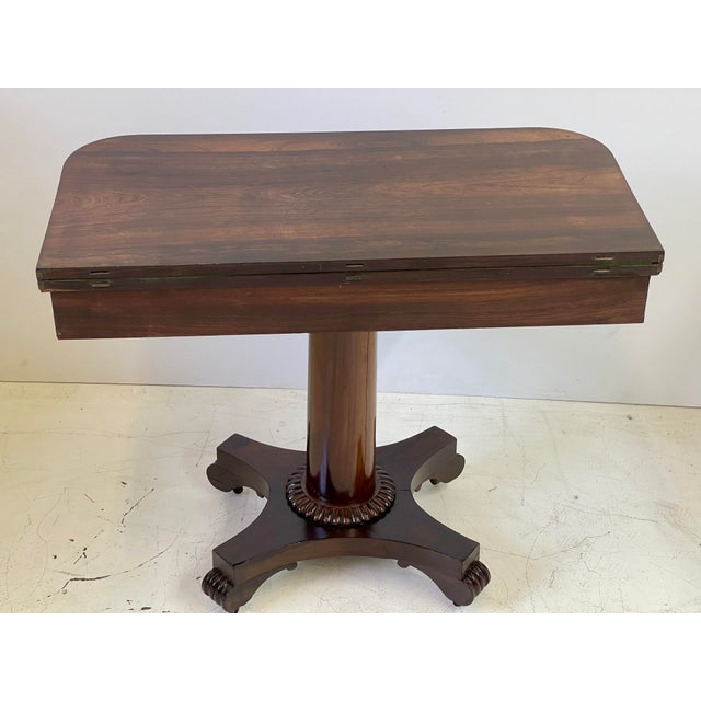 19th Century English fold-over games table made of rosewood in the Regency style. The table top spins and opens to provide...