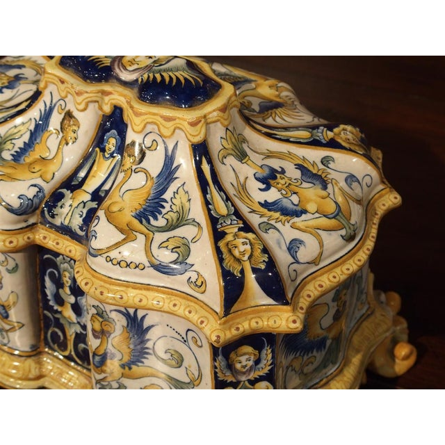 From 19th Century Italy, this shaped majolica box has hand painted, female, winged, half-figure motifs with varying...