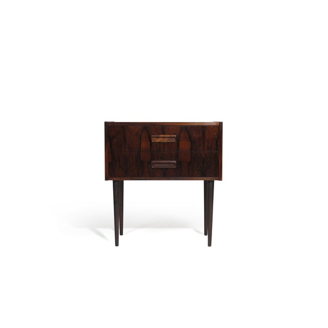 Pair of mid-century Danish nightstand bedside tables crafted of Brazilian rosewood veneer with dynamic pattern matched...
