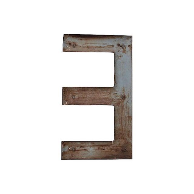 "Large vintage metal sign letter ""E"" with original blue painted finish. Metal tabs on back for hanging."
