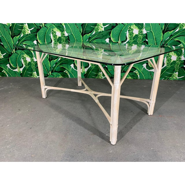 Vintage rattan dining table features large glass top and cathedral style detailing. Very good condition with minor...