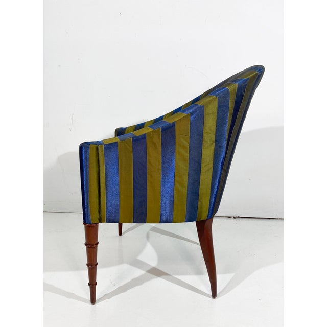 A Stylish and petite upholstered club or tub chair on turned front legs in the front and tapered saber legs in back;...