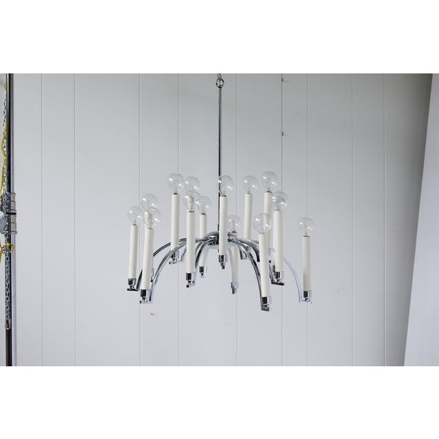 Mid-20th century chandelier made of chrome with 14 downswept arms supporting modern candlesticks holding chandelier bulbs....