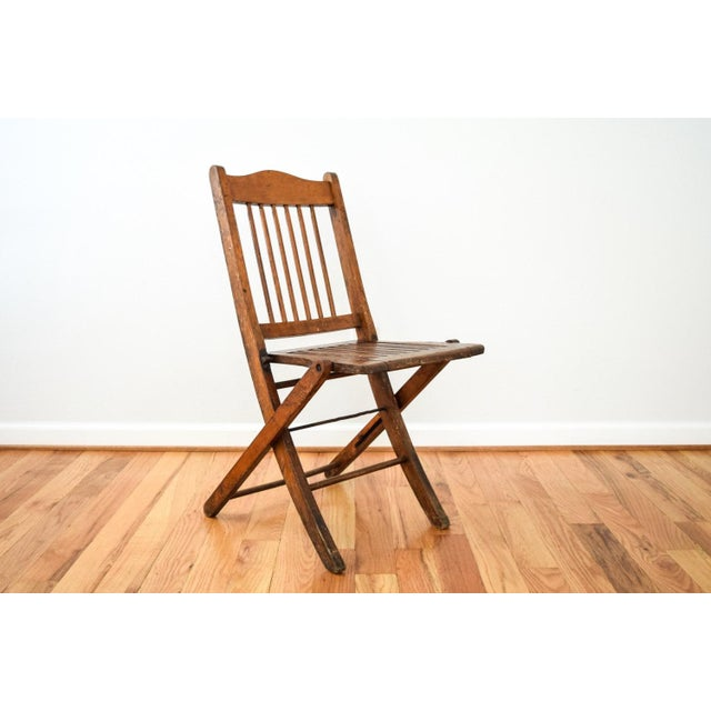 • Antique folding chair circa early 20th c. • Classic theater or deck style. • Well constructed with slatted seat and...