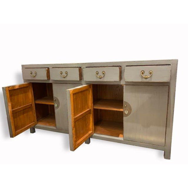 An amazing and beautiful gray buffet table with lots of storage. Has 4 drawers and 4 doors, delicately made with our...