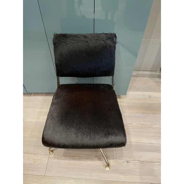 Minimal swivel chair made of fine black cow hair hide upholstered on a brass base. This understated piece has a lot of...