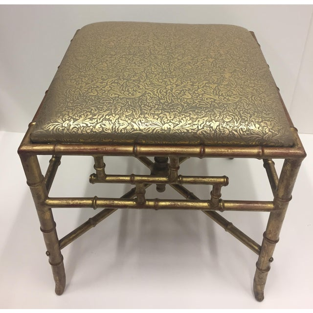 A glitzy and elegant Italian gilded iron ottoman bench having subtle red under-paint on its faux bamboo base and gorgeous...