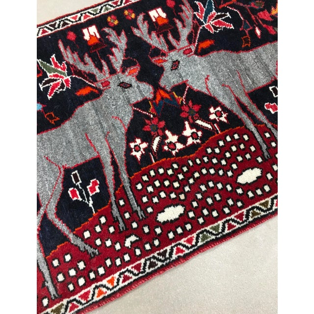 A charming little Persain hand knitted wool rug depicting two reindeer. A new, unused rug in excellent condition.