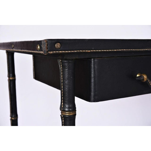 Jacques ADNET - Original black leather stitched desk with oak wood veneer and brass accents. Two drawers. c. 1950