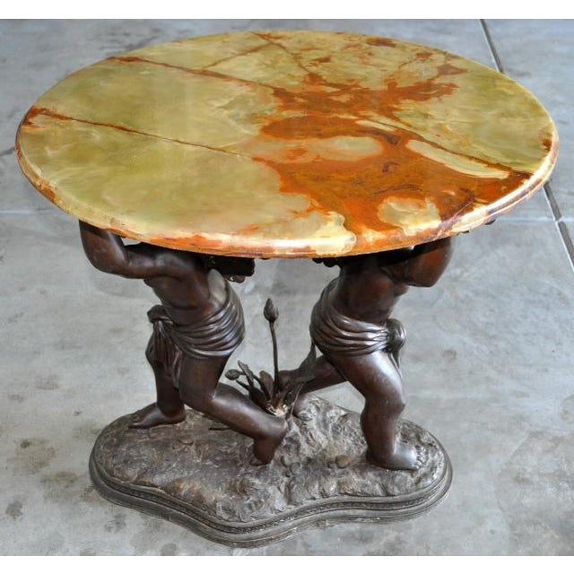 This is a vintage Renaissance style table which has a bronze base depicting two cupids with wings. The cupids are holding...
