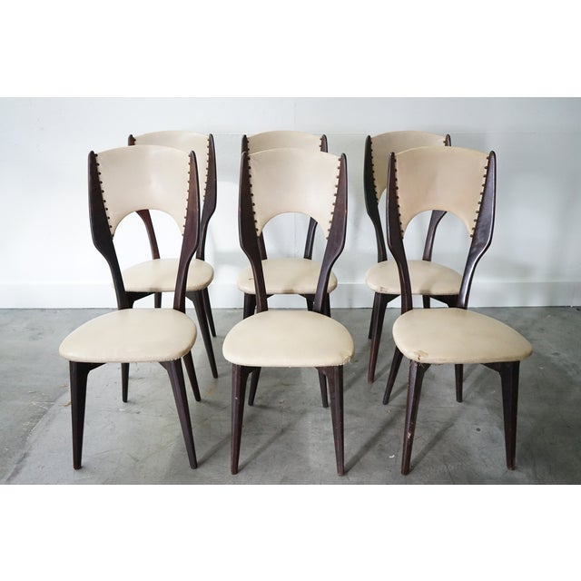 A beautiful set of six mid-century modern dining chairs complete with beautiful wooden teak frames, vintage leather...