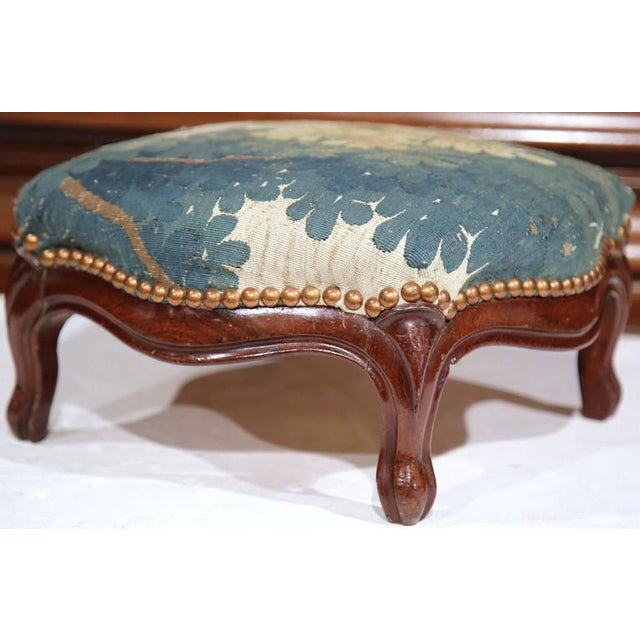 This Classic, antique fruitwood stool was crafted in France, circa 1840. The wooden base of the stool is carved and has...