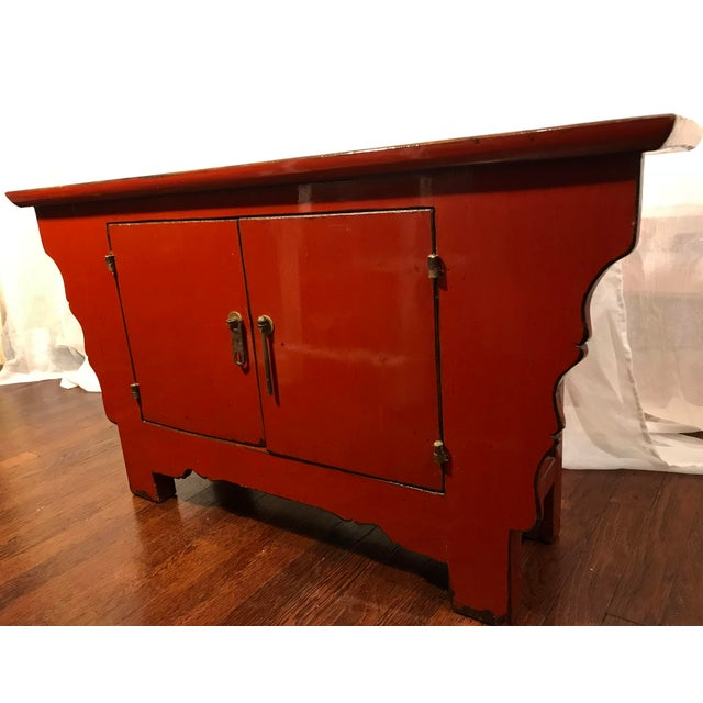 Lovely vintage deep orange red cinnabar rustic lacquered Chinese alter cabinet, sideboard, buffet. Two shelves span the...