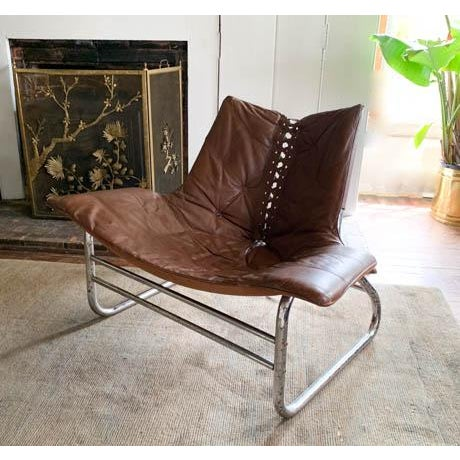 Quite simply a statement chair. It commands the room. Mid century. Brown leather and a tubular chrome base. Wing like...