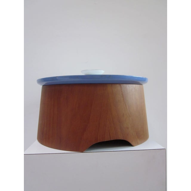 Stunning blue enamel casserole paired with a wood carrier holder, believed to be teak wood, that fits casserole perfectly....