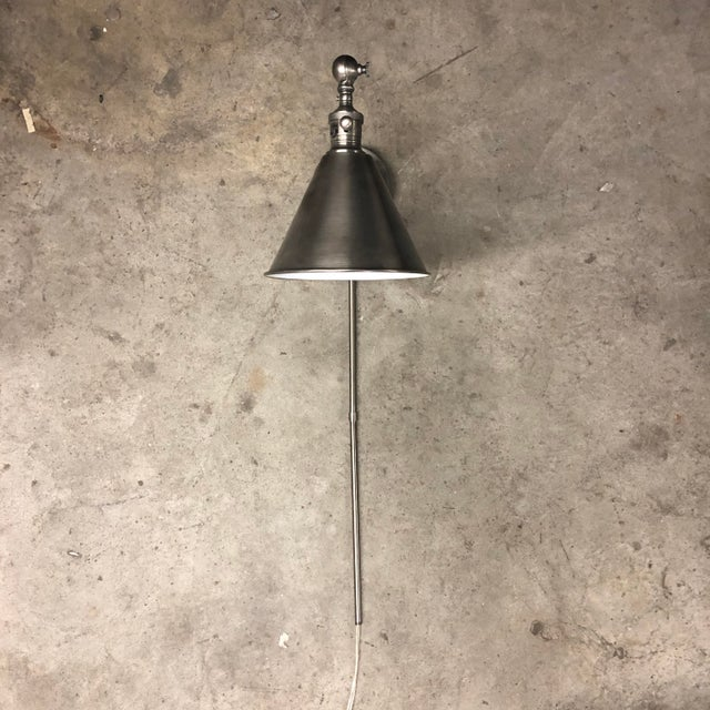 An E.F. Chapman styled antiqued nickel library wall light with a single arm. The light fixture plugs into an outlet and...