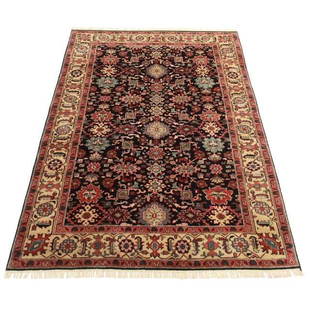 This is a hand knotted wool Indian rug with all over design in hues of crimson, cream, black and bits of baby blue and green.