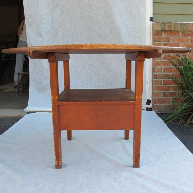 """18th-Century New England Round Hutch Table. Red painted base with a scrubbed top. One leg has a 1"""" tab. Two legs have a..."""