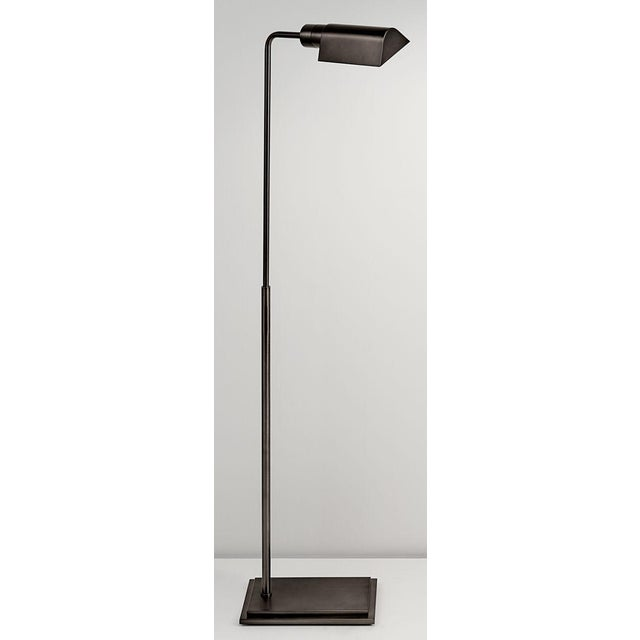 A black bronze lamp with a rectangular stepped base and tubular column with a triangular canopy. The upright column...