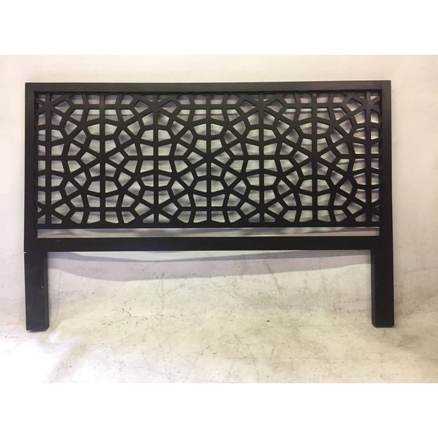 This painted black wooden headboard almost resembles a fractal, floral design with its geometric latticing throughout. A...