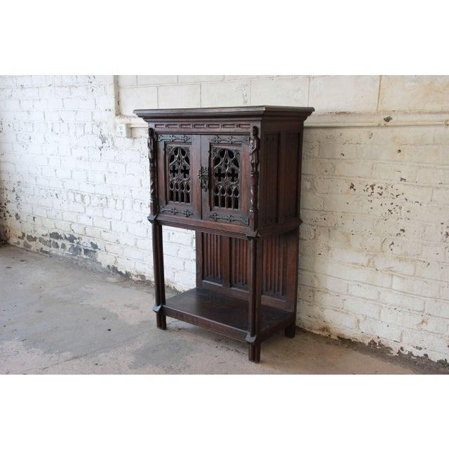 Offering a very nice and rare antique Belgian dark oak gothic bar cabinet. This piece has hand carved Belgian guardsmen on...