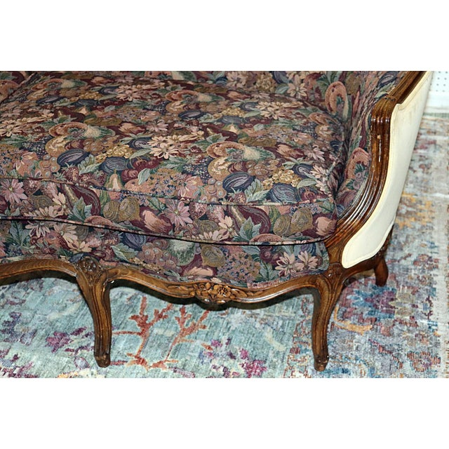 Louis XV style carved walnut sofa with floral machine tapestry upholstery.